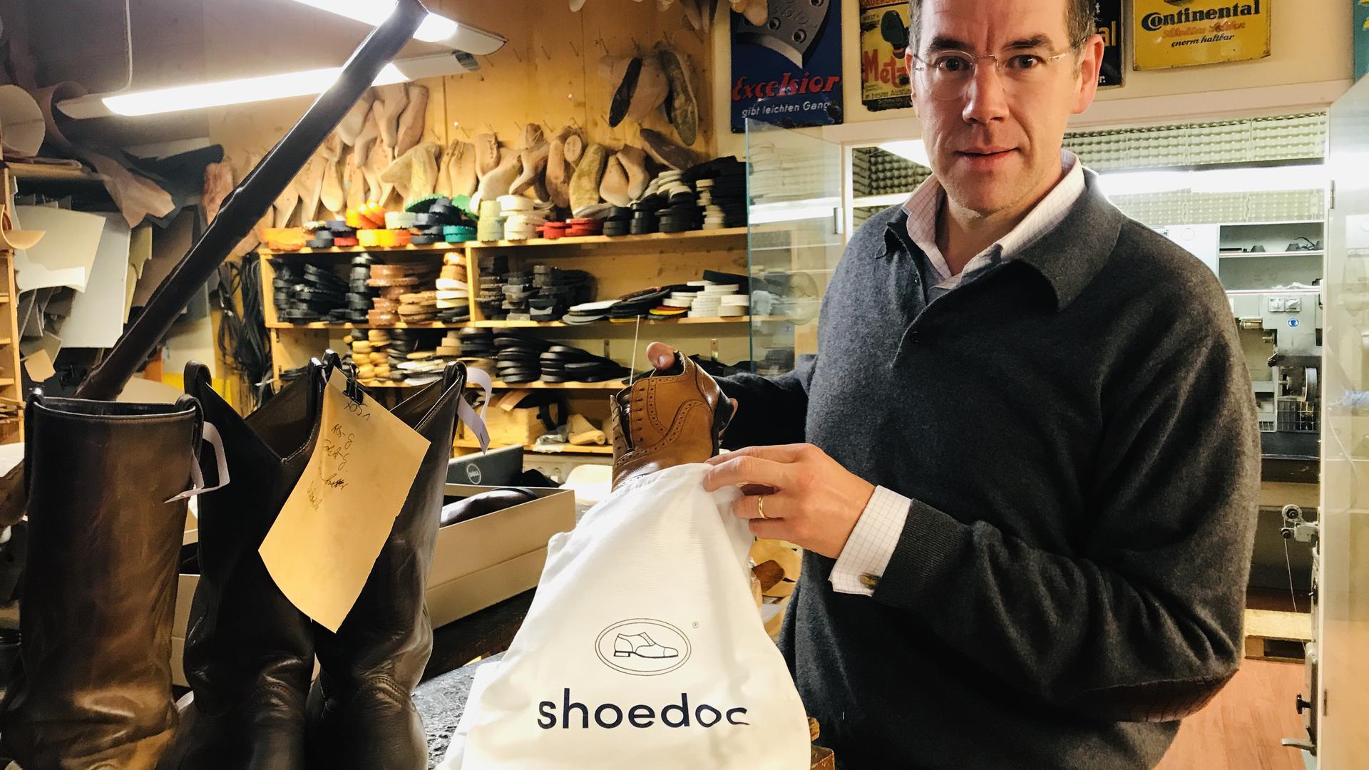 Ein Mann steht in einer Schuhwerkstatt und packt einen reparierten Herrenschuh in einen weißen Beutel