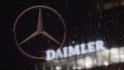 Das Logo der Daimler-AG ist an der Konzernzentrale zu sehen, im Vordergrund ist ein Mercedes-Stern auf einer Flagge abgebildet, die voller Regentropfen ist.