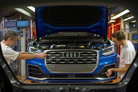 Fertigungsmechaniker bringen an einem Fließband im Audi-Werk die Front an einem Audi an.