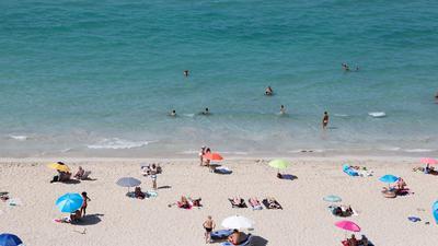 Badegäste am Strand von Arenal auf Mallorca. Deutsche Tourismuskonzerne kritisieren die Reisewarnung des Auswärtigen Amtes für die spanische Insel.
