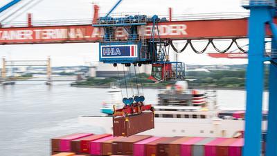Ein Container wird auf dem Terminal Altenwerder im Hamburger Hafen auf ein Schiff geladen. Deutschlands Exporteure arbeiten sich langsam aus dem Corona-Tief.