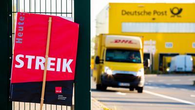 """Ein Schild der Gewerkschaft Verdi mit der Aufschrift """"Heute Streik"""" steht vor einer Deutsche-Post-DHL-Niederlassung."""