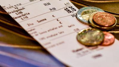 Wechselgeld liegt auf dem Kassenbon in einer Metzgerei.