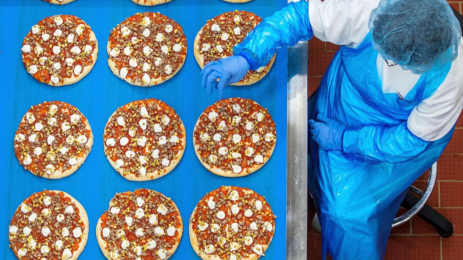 Mitarbeiterinnen kontrollieren im Pizzawerk der Firma Dr. Oetker in Wittenburg die gleichmässige Verteilung des Belags auf Pizzen.