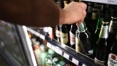 Ein Mann holt eine Flasche Bier aus einem Kühlschrank in einem Spätkauf in Berlin-Mitte.