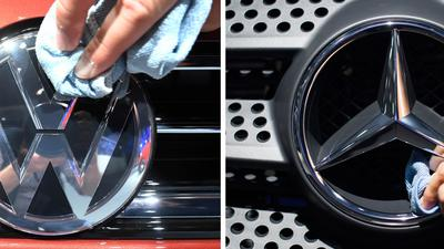 Mitarbeiter der deutschen Automobilmarken BMW Volkswagen (l) und Daimler polieren die Logos der jeweiligen Fahrzeuge.