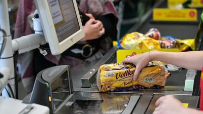Eine Kassiererin an der Kasse. Gedämpft von der Mehrwertsteuersenkung ist die Inflation in Deutschland im September erneut unter die Nullmarke gerutscht.