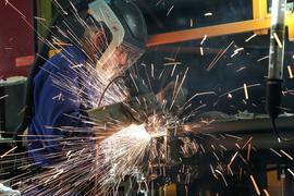 Ein Mitarbeiter eines Unternehmen imBereich Maschinenbau schneidet mit einem Trennschleifer korrodierte Metallteile aus dem Träger eines Wagenkastens einer S-Bahn.