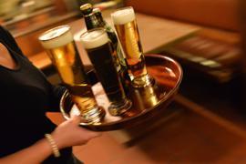 Eine Kellnerin trägt Bier auf einem Tablett.