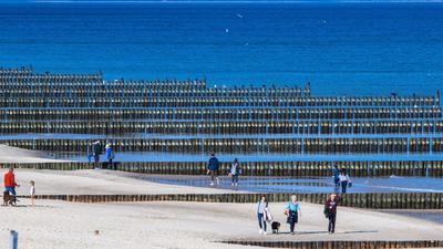 Spaziergänger am Strand von Koserow auf der Ostseeinsel Usedom.