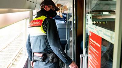 Ein Mitarbeiter der DB-Sicherheit kontrolliert in einem ICE, ob die Fahrgäste einen Mund-Nasen-Schutz tragen.