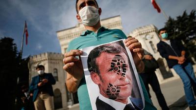 Ein junger Mann hält ein mit einem Schuhabdruck versehenes Foto von Emmanuel Macron, Präsident vonFrankreich, in die Kamera. Recep Tayyip Erdogan, Präsident der Türkei, griff Macron ein zweites Mal verbal an und warf ihmIslamfeindlichkeit vor.