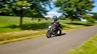 Ein Motorradfahrer fährt mit einem Leichtkraftrad mit 125ccm über eine Landstraße im Westerwald.