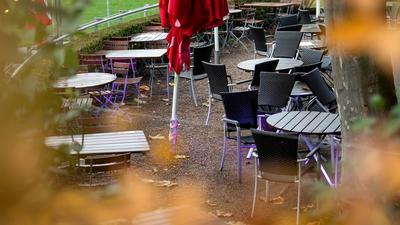 Leere Tische und Stühle stehen vor einem Restaurant.