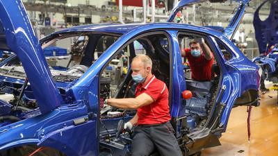 Mitarbeiter von Porsche arbeitenin der MontageaneinemPorsche Macan.
