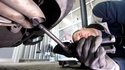 Ein Mitarbeiter vom TÜV Nord überprüft im Rahmen einer Abgasuntersuchung (AU) mit einer Sonde für den Auspuff einen Wagen mit Diesel-Motor.