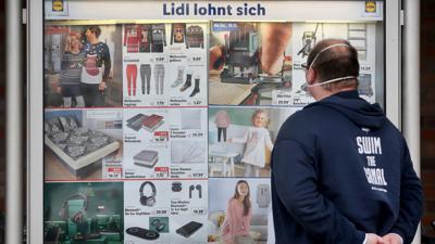 Ein Kunde einer Lidl-Filiale informiert sich an einer Werbetafel über die Sonderangebote.