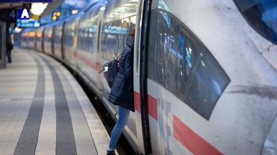 Ein Fahrgast steigt in einen Fernzug der Deutschen Bahn. Die EVG spricht sich gegen eine Reservierungspflicht in Zügen aus.