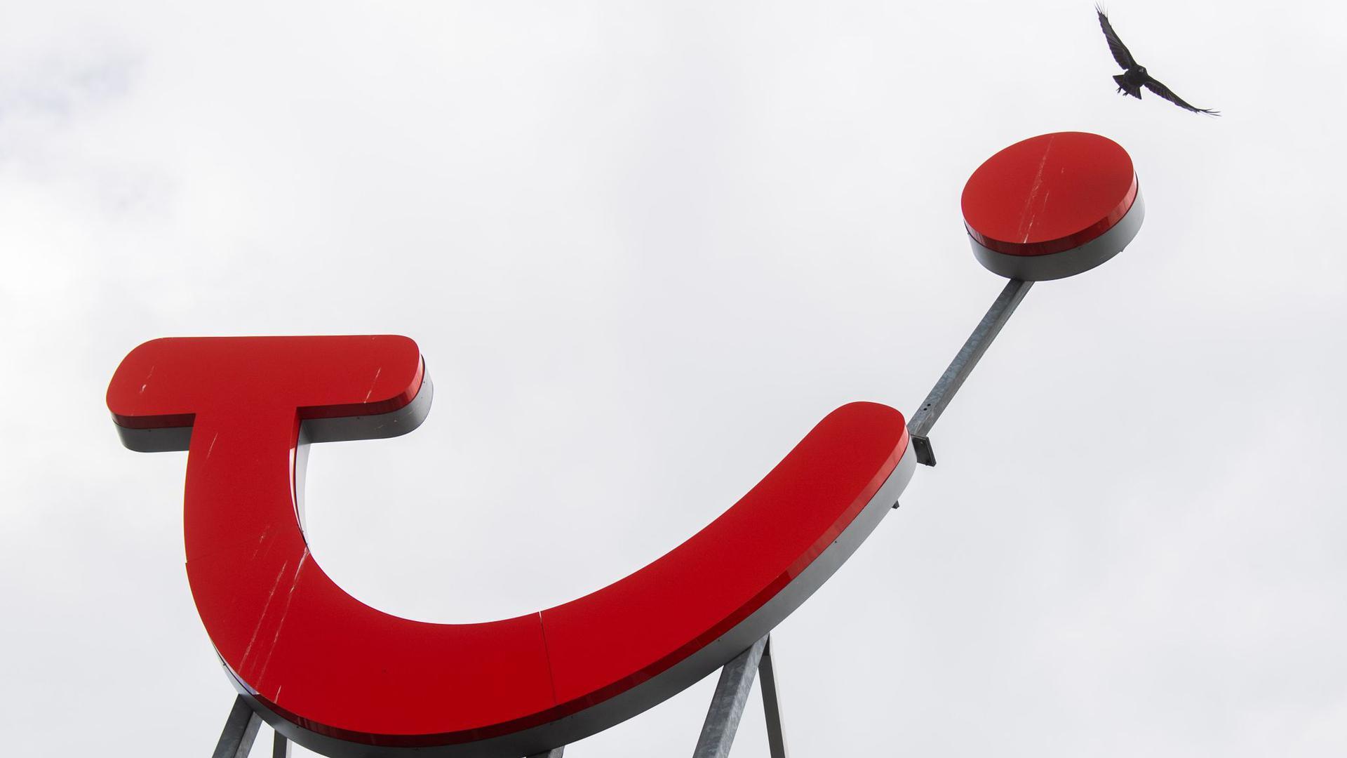 Eine Krähe fliegt über das Logo der Tui Group am Firmensitz.