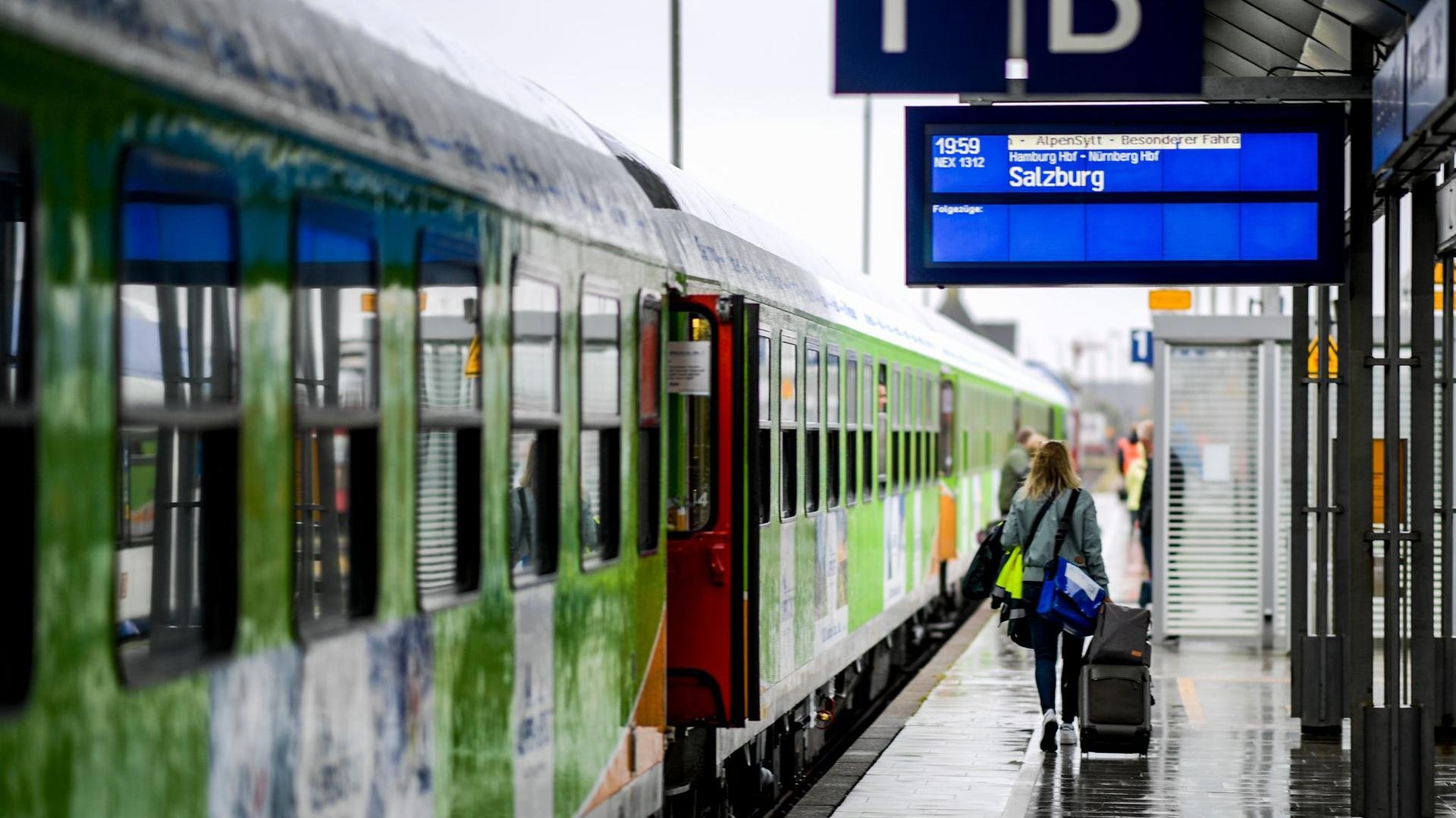 Fahrgäste des neuen Alpen-Sylt-Nachtexpress von Sylt nach Salzburg des Bahnanbieters RDC laufen kurz vor der Abfahrt des Zuges über den Bahnsteig.
