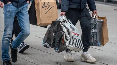 Junge Männer schleppen Einkaufstüten, während auf der Frankfurter Einkausmeile Zeil am Samstag des zweiten Adventswochendes reger Betrieb herrscht.