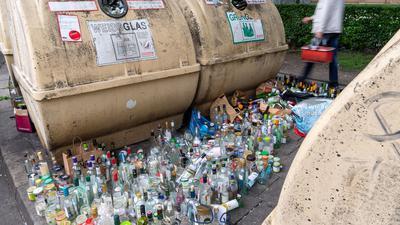 Hunderte Glasflaschen stehen neben vollen Containern am Strassenrand im Stadtteil Haidhausen in München.