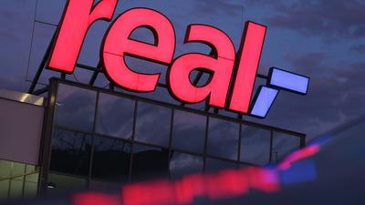 Das Logo leuchtet am Morgen auf dem Dach eines Real Supermarktes.