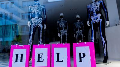 Schaufensterfiguren, die Anzüge mit Skelettmotiv und Mund-Nasen-Schutz tragen, stehen in einem geschlossenen Geschäft in der Innenstadt von Köln.