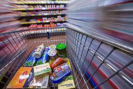 Lebensmittel liegen in einem Markt in einen Einkaufswagen. Die Corona-Krise hat den Anstieg der Verbraucherpreise 2020 stark gebremst.