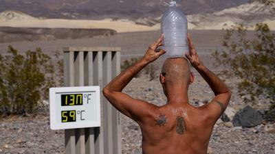 """Ganz schön heiß:Ein Mann kühlt sich im """"Death Valley""""-Nationalpark im US-Bundesstaat Arizona bei 59 Grad Hitze mit einer mit Eiswasser gefüllten Plastikflasche auf dem Kopf ab (Archiv)."""