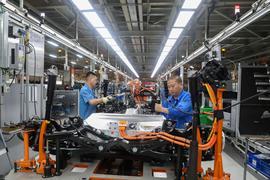 Fahrzeugbauer arbeiten in einer Werkshalle in Shanghai an einer Produktionslinie von SAIC Volkswagen.