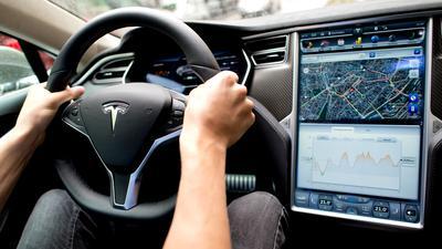 Ein Mann sitzt in einem Tesla Model S amLenkrad, neben ihm ein großer Monitor imArmaturenbrett.