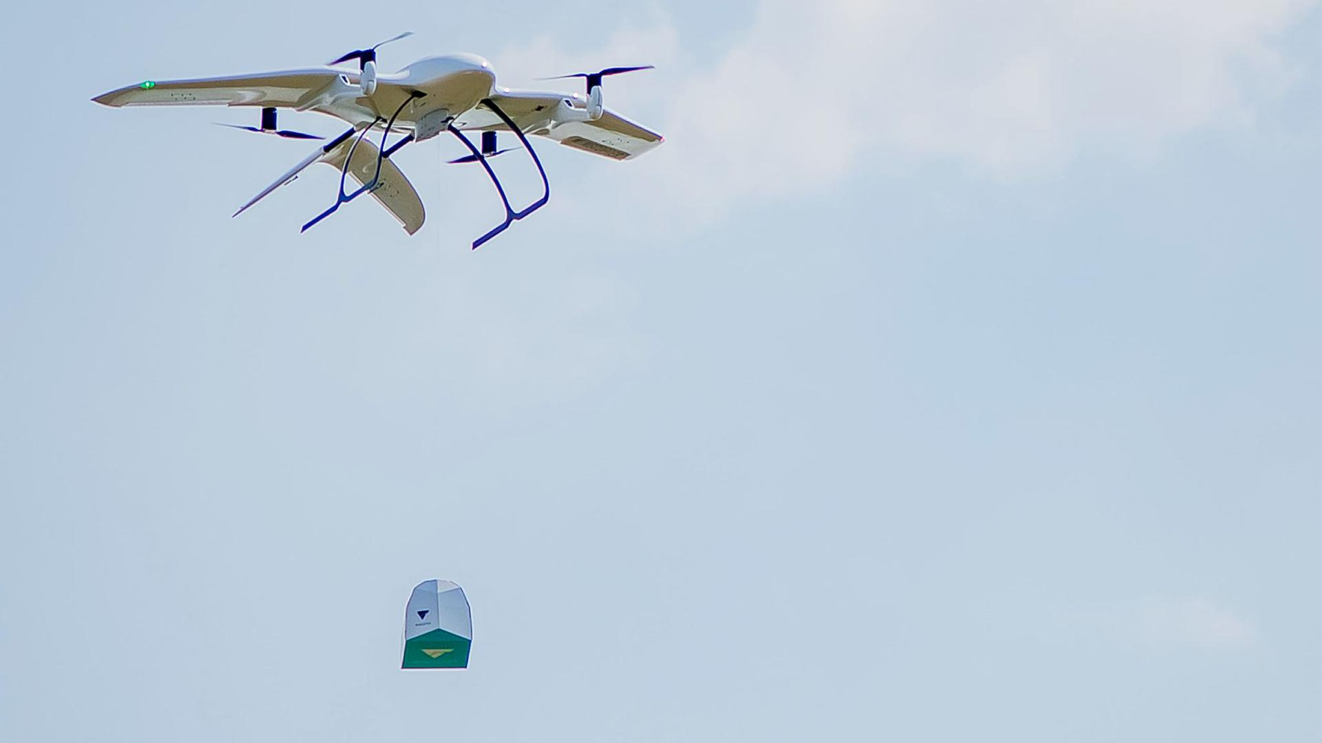 Eine Drohne des Start-Ups Wingcopter trägt ein Paket. Das mit Tragflächen ausgestattete Gerät kann senkrecht aufsteigen und dann auf der Strecke auch bei widrigen Wetterverhältnissen wie ein Propeller-Flugzeug fliegen.