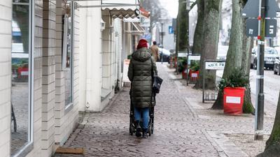 Eine Frau geht in Ahrensburg bei Hamburg durch eine leere Einkaufsstrasse.