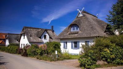 Reetgedeckte Ferienhäuser stehen auf der Ostseeinsel Poel.