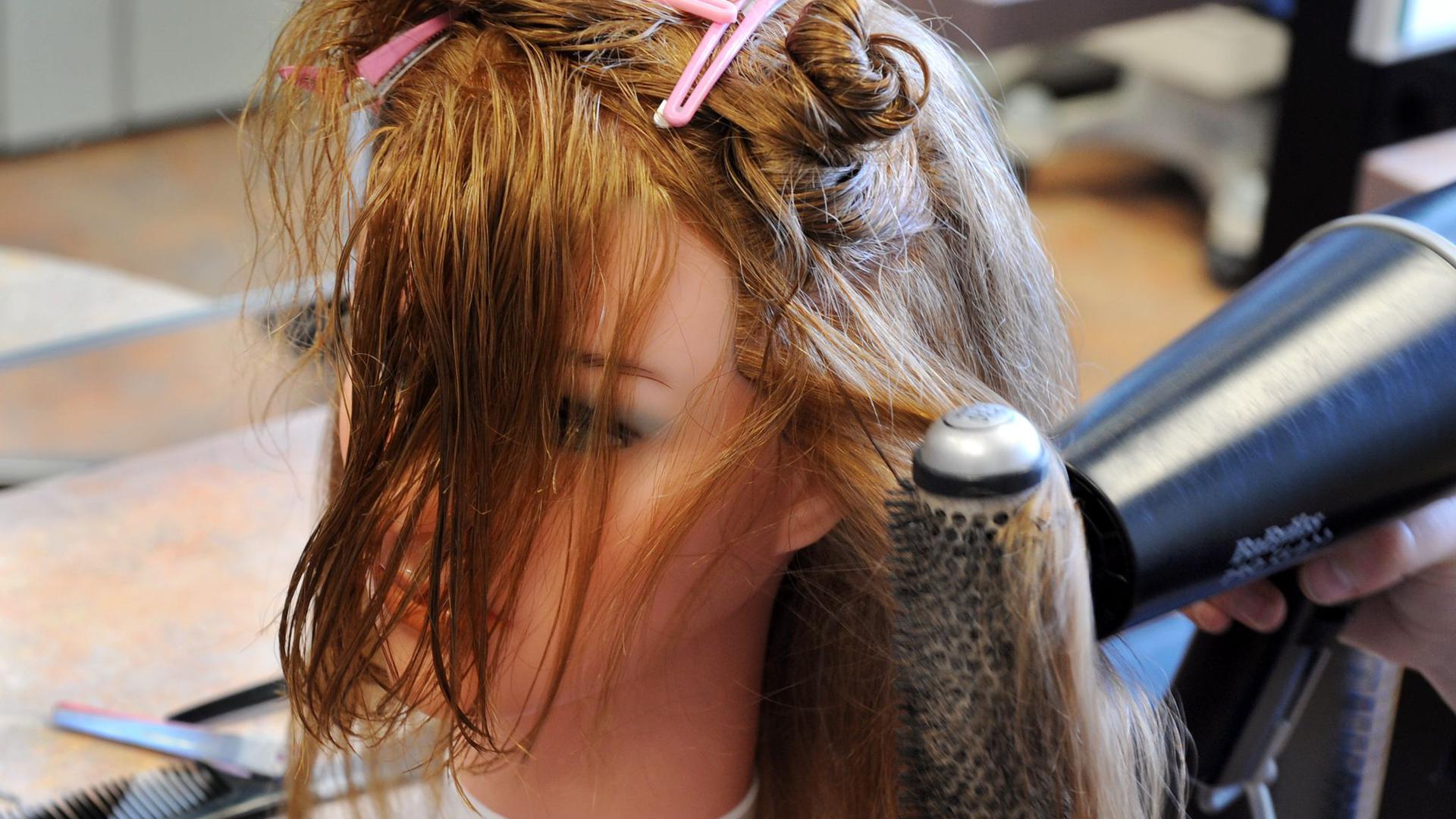 Friseur-Übung an einem Übungskopf.