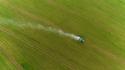 Ein Traktor fährt bei Gammelin über einen Acker und verteilt mit einem Streuer Pflanzendünger.