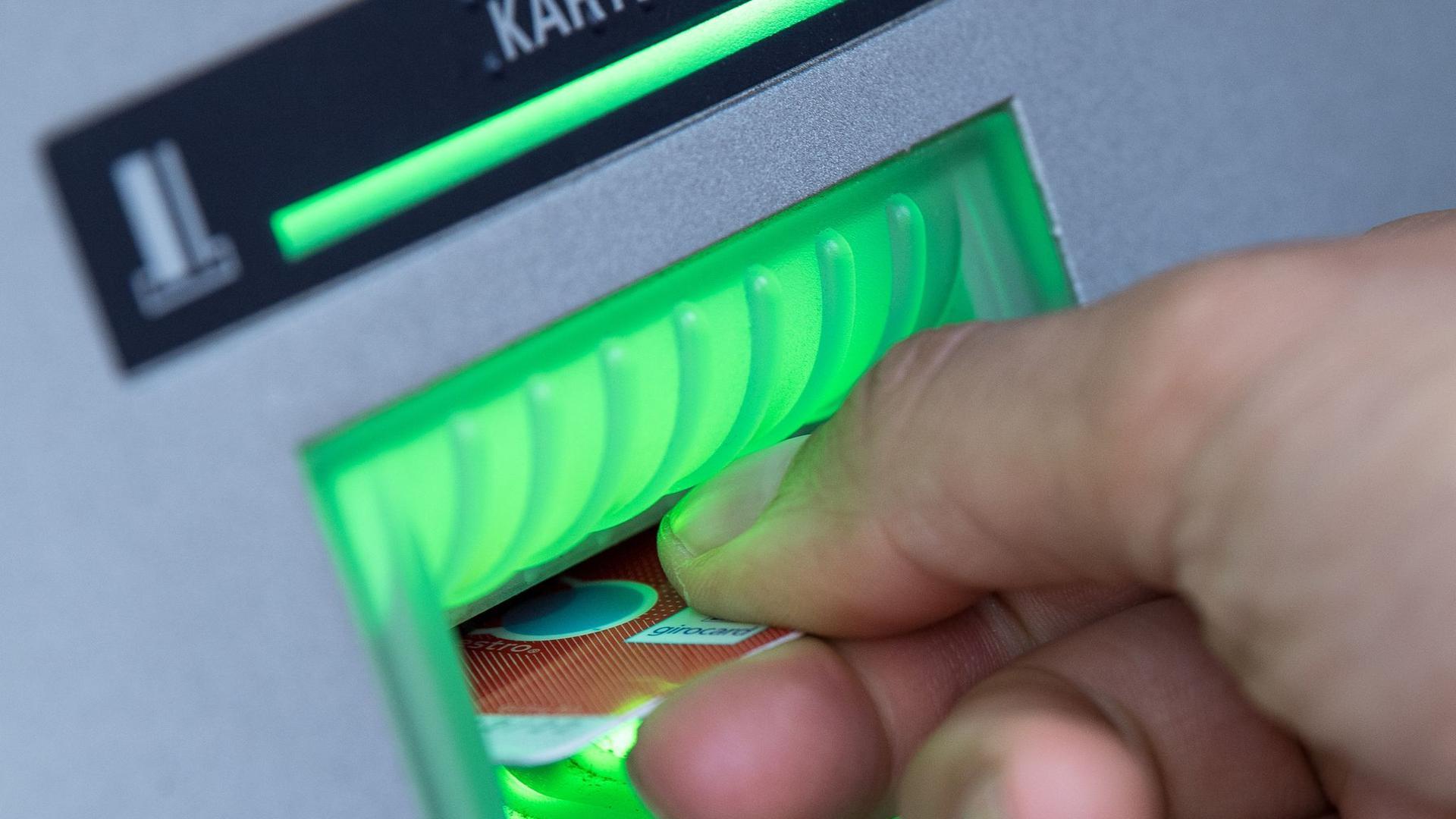 Eine Bankkundin steckt ihre Girokarte in einen Geldautomaten.