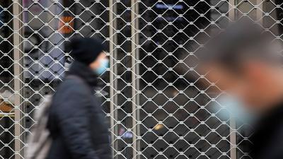 Menschen mit Mundschutz gehen an einem geschlossenen Geschäft in der Stuttgarter Innenstadt vorbei.