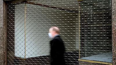 Ein Mann geht an einem leerstehenden Ladenlokal in Köln vorbei.