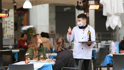 Ein Kellner bedient zwei Kundinnen auf der Terrasse einer Bar im Zentrum von Madrid.