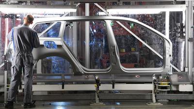 Ein Mitarbeiter arbeitet im VW-Werk in Emden an der Karosserie eines VW.