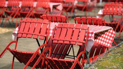 Stühle und Tische stehen auf einer Außengastronomiefläche eines Ausflugslokales.