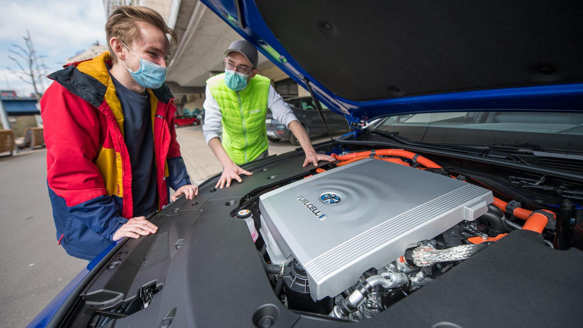Fahrlehrer Rouven Klein (r) und Fahrschüler Adrian Bredebusch schauen auf die Brennstoffzelle des Wasserstoff-Fahrschulautos der Fahrschule VooVooDrive in Saarbrücken.