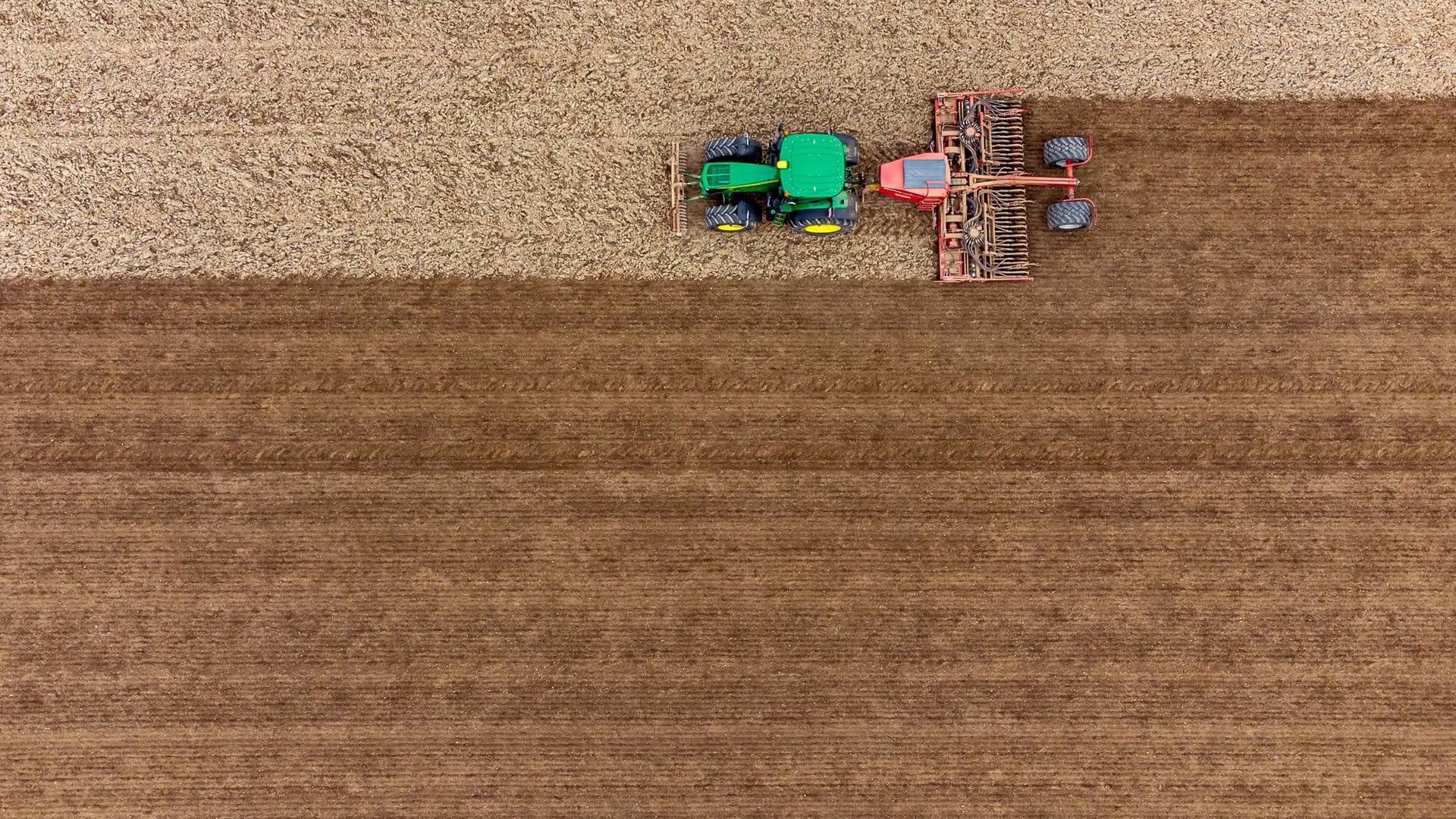 Auf einem Feld wird mit einer Drillmaschine Saatgut von Braugerste angebaut (Luftaufnahme mit Drohne).