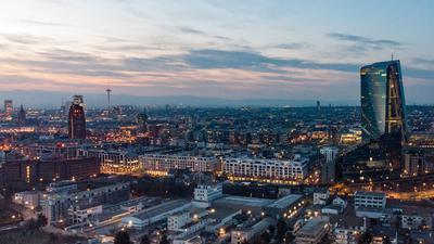 Die Bankentürme der Innenstadt und die Lichter in den Büros der Europäischen Zentralbank (EZB) leuchten im Abendlicht.