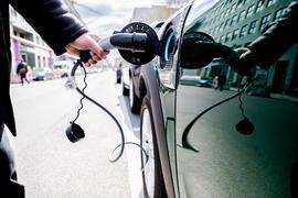 Ein Mann nimmt an einem Auto mit Plug-in-Hybrid-Antrieb in Berlin-Mitte den Ladestecker raus.