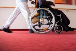 Ein Pfleger schiebt die Bewohnerin eines Pflegeheims in einem Rollstuhl.