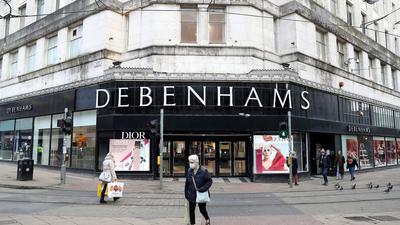 Menschen gehen auf der Market Street in Manchester an Debenhams vorbei.