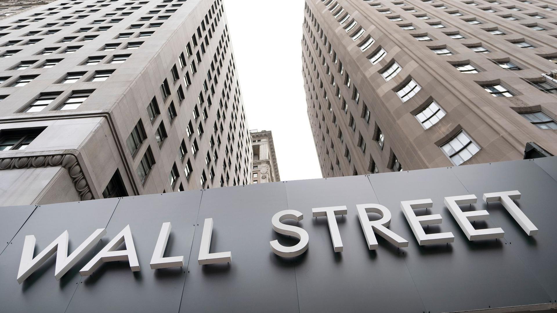 """Ein Schild mit der Aufschrift """"Wall Street"""" hängt an der Fassade der New Yorker Börse."""